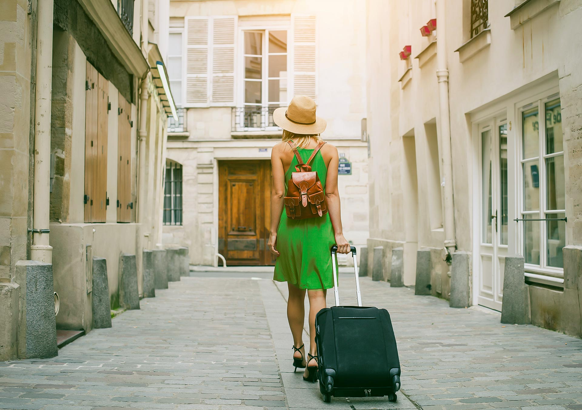A young lady in a green dress walking down a street in Europe, trailing her suitcase behind her